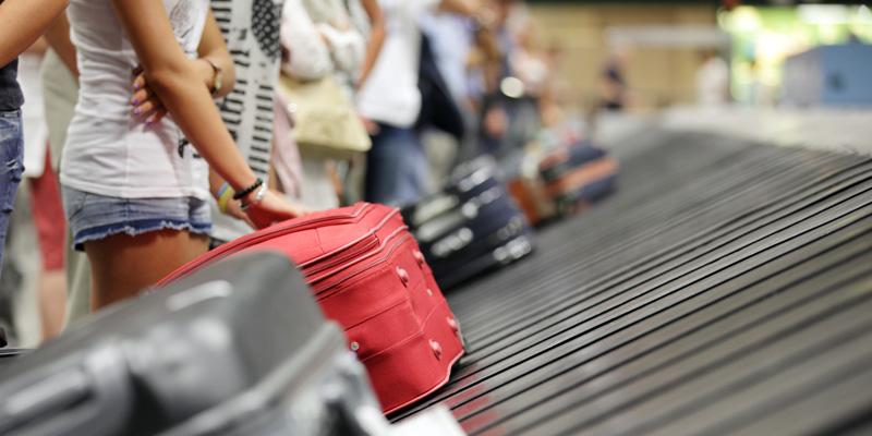 Människor väntar på sina resväskor vid ett rullband