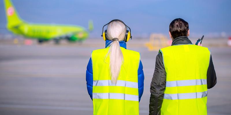 Två personer med reflexvästar står ute på en flygplats