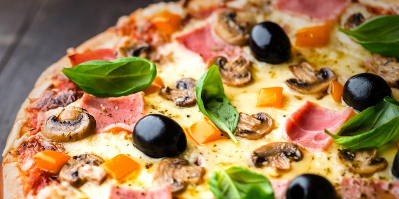 Pizza med skinka, ost, champinjoner, oliver och basilika
