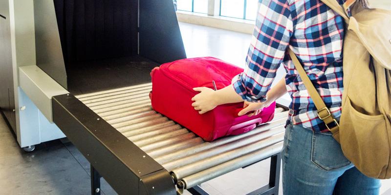 En resenär lägger en resväska på ett rullband vid säkerhetskontrollen.
